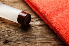 Toiletry tube and towel scene. The towel and toiletry tube on wooden floor surface represent the toiletry material and travel industry concept related idea Royalty Free Stock Images