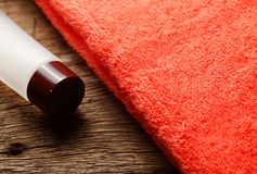 Toiletry tube and towel scene. The towel and toiletry tube on wooden floor surface represent the toiletry material and travel industry concept related idea Stock Photo