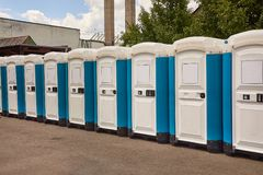 Toilets installed at a public event. Long row of mobile toilets stock photo