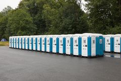 Toilets installed at a public event. VIZOVICE, CZECH REPUBLIC - JULY 11, 2018: Long row of portable toilets for the Masters Of Rock festival beginning the next stock photography