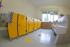 Toilets of the school and ceramic sinks and yellow doors without. Clean toilets of the school and ceramic sinks and yellow doors without the kids and a bright royalty free stock image