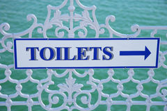 Toilets sign. A toilets sign with the sea as background on  a squiggly railing Stock Photography