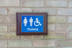 Toilets sign for public restroom. Mounted on a brick wall Royalty Free Stock Image