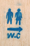 Toilets to right. Toilet to right. Restroom sign on grunge wall Stock Photos