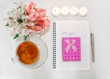 Toilettafel met women' s toebehoren Het beeld van een roze giftdoos met een boeket van Alstroemeria bloeit, kaarsen, koppen  stock foto