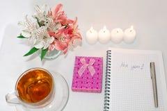 Toilettafel met women' s toebehoren Het beeld van een roze giftdoos met een boeket van Alstroemeria bloeit, kaarsen, koppen  royalty-vrije stock foto's