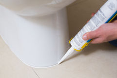 Toilette de fixation de plombier dans une salle de toilette avec la cartouche de silicone Photo stock