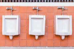 Toilette des Mannes Fliesen ummauern in der Toilette des Mannes mit vielen Toilette lizenzfreie stockfotografie