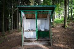 Toilette im Freien mit zwei Sitzen in einem Wald Stockbild