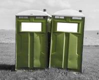 Toilette mobile verte sur une plage noire et blanche Photographie stock libre de droits