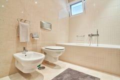Toilette moderna con le piastrelle di ceramica ed il bagno. Fotografia Stock