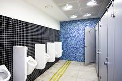 Toilette publique avec des compartiments et des urinaux Image libre de droits