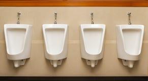 Toilette pulite dell'uomo quattro dell'orinale nelle toilette pubbliche Immagine Stock