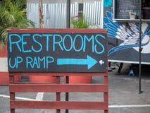 Toilette scritte a mano blu sul segno della rampa sul bordo di gesso che indica destra fotografie stock libere da diritti