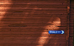 Toilette sign at a wooden block house Royalty Free Stock Photography