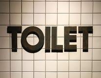 Toiletten-Wort gemacht vom rustikalen Metall in der Weinlese-Design-Art gesetzt wie 3D auf die weiße Luxustoilette mit Ziegeln ge Stockfoto
