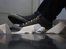 Toilettenpapier und Schuhe auf dem Boden stockfoto