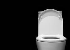Toilettenschüssel mit schwarzem Hintergrund Stockbilder