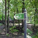 Toilettenzeichen unter Bäumen Stockfotos