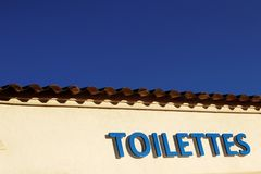 Toilettes Sign under blue sky. Outdoor toilets sign on an yellow wall under deep blue summer sky near Saint Tropez beach, French riviera, Var, Provence, France stock image