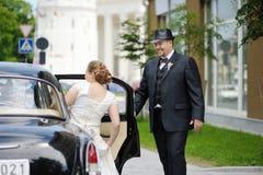 Toilettez aider sa jeune mariée à entrer dans une voiture Photos stock
