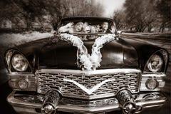 Toilettez et la jeune mariée à une roue d'un vieux rétro noir de la voiture Photo stock