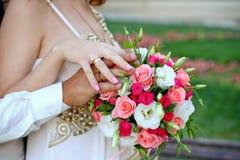 Toilettez et la jeune mariée avec un plan rapproché de bouquet de mariage dehors Images stock