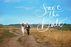 Toilettez et la jeune mariée marchant sur le champ pendant le jour du mariage et les mots font gagner la date Lettrage de calligr Photographie stock libre de droits
