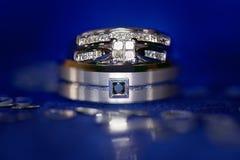 Toilettez l'anneau de mariage du ` s avec des anneaux du ` s de jeune mariée équilibrés sur le dessus Photographie stock libre de droits