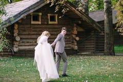 Toilettez l'avance sa jeune mariée à la maison en bois dans le mariage d'automne de forêt dessin-modèle Photographie stock libre de droits