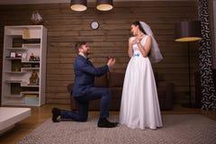 Toilettez la position sur ses genoux contre la jeune mariée heureuse Photos stock