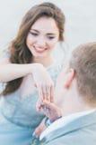 Toilettez le souhait pour embrasser la main de la jeune mariée au bord de la mer Image stock