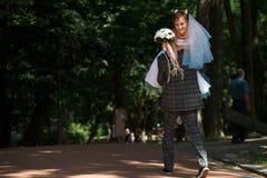 Toilettez porter la jeune mariée sur le parc de fond Photographie stock libre de droits