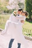 Toilettez porter sa belle jeune mariée sur des bras se penchant des fronts au parc de ressort Photographie stock libre de droits