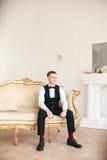 Toilettez se reposer sur le sofa attendant la jeune mariée son jour du mariage à la jeune mariée de sourire et de attente de smok Image stock