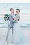 Toilettez se tenir dans la jeune mariée de bras par la mer Photographie stock libre de droits