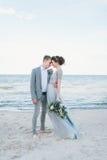 Toilettez se tenir dans la jeune mariée de bras par la mer Photos libres de droits