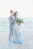 Toilettez tenir la jeune mariée dans le voile par la mer Photos stock