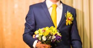 Toilettez tenir le bouquet de mariage, fleurs dans des mains masculines photo libre de droits