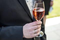 Toilettez tenir le vin mousseux en verre épousant l'anneau rouge de plan rapproché de costume de champagne Image libre de droits