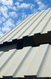 Toit à deux niveaux de fer ondulé contre le ciel nuageux Image libre de droits