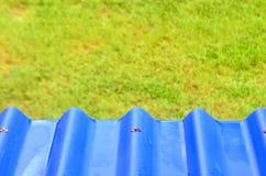 Toit bleu avec le champ vert Photos stock