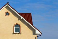 Toit d'une nouvelle maison construite avec la fenêtre et la cheminée intéressantes Images libres de droits