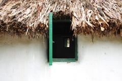 Toit de fenêtre et de paille d'ancienne maison slave Image stock