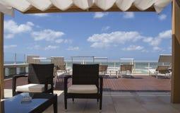 Toit devant la mer avec les lits bronzés, les armchais, le ciel bleu et les nuages blancs photos stock
