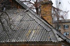Toit et cheminée d'ardoise endommagés très vieux d'amiante Images libres de droits