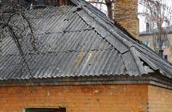 Toit et cheminée d'ardoise endommagés très vieux d'amiante Photos stock