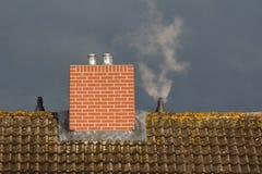 Toit et cheminée sur le fond du mauvais temps Photo libre de droits