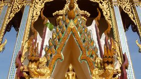 Toit ornemental de temple oriental Toit ornemental d'or de temple asiatique traditionnel contre le ciel bleu sans nuages dessus banque de vidéos