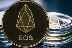Token cryptocurrency EOS on the background of a stack of coins. New token cryptocurrency EOS on the background of a stack of coins stock photo